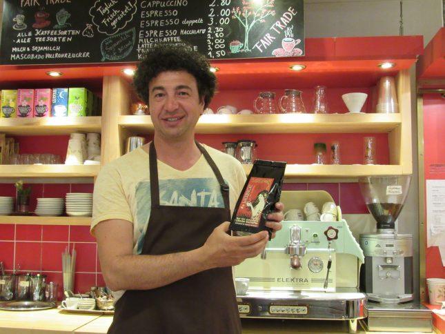 """Aykut Kayabas, Inhaber der """"ONE Fairtrade Kaffeerösterei"""", mit einem seiner Lieblingsprodukte, dem Stadtkaffee """"Liubice"""" – wie alles andere im Geschäft bio und fair gehandelt."""